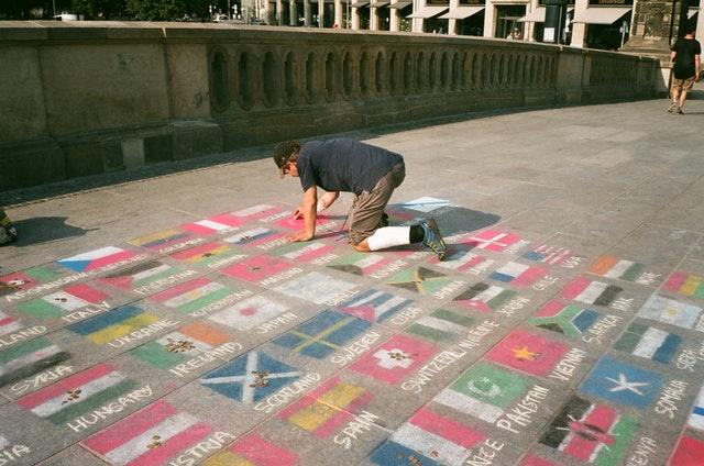 La imagen muestra un chico pintando banderas en el suelo